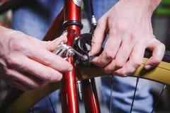 题材修理自行车 一个白种人人` s手用途的特写镜头手工工具六角形集合调整和安装外缘闸在一红色bicy 库存照片