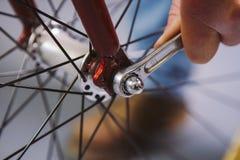 题材修理自行车 一个白种人人` s手用途的特写镜头手工工具自行车用工具加工插孔锥体Wrenc调整和安装 图库摄影