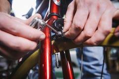 题材修理自行车 一个白种人人` s手用途的特写镜头手工工具六角形集合调整和安装外缘闸在a 免版税库存照片