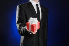 题材假日和礼物:一套黑衣服的一个人在有白色丝带的红色在深蓝b的箱子和弓拿着专属礼物被包裹 库存照片