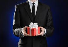 题材假日和礼物:一套黑衣服的一个人在有白色丝带的红色在深蓝b的箱子和弓拿着专属礼物被包裹 免版税库存照片