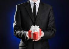 题材假日和礼物:一套黑衣服的一个人在有白色丝带的红色在深蓝b的箱子和弓拿着专属礼物被包裹 库存图片
