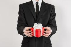 题材假日和礼物:一套黑衣服的一个人在有白色丝带的红色在wh隔绝的箱子和弓拿着专属礼物被包裹 库存图片