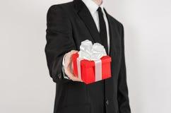 题材假日和礼物:一套黑衣服的一个人在有白色丝带的红色在wh隔绝的箱子和弓拿着专属礼物被包裹 免版税库存照片