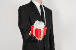 题材假日和礼物:一套黑衣服的一个人在有白色丝带的红色在wh隔绝的箱子和弓拿着专属礼物被包裹 库存照片