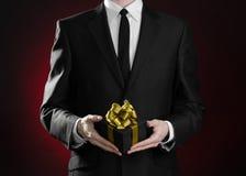 题材假日和礼物:一套黑衣服的一个人在有金丝带的一个在深红的黑匣子和弓拿着专属礼物被包裹 免版税库存图片