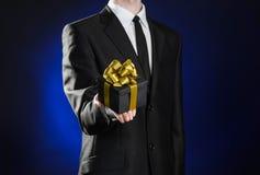 题材假日和礼物:一套黑衣服的一个人在有金丝带的一个在蓝色的黑暗的黑匣子和弓拿着专属礼物被包裹 库存照片