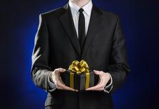 题材假日和礼物:一套黑衣服的一个人在有金丝带的一个在蓝色的黑暗的黑匣子和弓拿着专属礼物被包裹 免版税库存图片