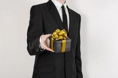 题材假日和礼物:一套黑衣服的一个人在有金丝带的一个在a隔绝的黑匣子和弓拿着专属礼物被包裹 免版税库存图片