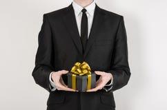 题材假日和礼物:一套黑衣服的一个人在有金丝带的一个在a隔绝的黑匣子和弓拿着专属礼物被包裹 免版税库存照片