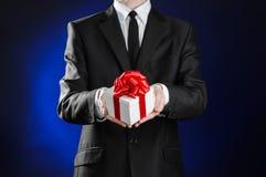 题材假日和礼物:一套黑衣服的一个人拿着在白色箱子的一件专属礼物包裹与红色丝带和弓在黑暗的b 库存照片