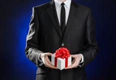 题材假日和礼物:一套黑衣服的一个人拿着在白色箱子的一件专属礼物包裹与红色丝带和弓在黑暗的b 免版税库存照片