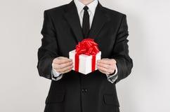 题材假日和礼物:一套黑衣服的一个人拿着在白色箱子的一件专属被隔绝的礼物包裹与红色丝带和弓  免版税库存照片
