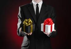 题材假日和礼物:拿着两份独家新闻礼物的一套黑衣服的一个人被包装在有金丝带的一个黑匣子和弓和a 免版税库存照片