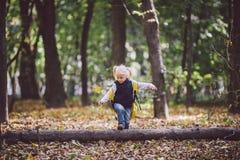 题材儿童室外活动 白种人白肤金发的女孩通过克服障碍的滑稽的矮小的婴孩,树的森林走跌倒了 免版税库存图片