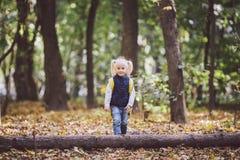 题材儿童室外活动 白种人白肤金发的女孩通过克服障碍的滑稽的矮小的婴孩,树的森林走跌倒了 库存图片