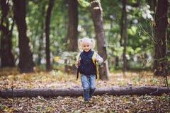 题材儿童室外活动 白种人白肤金发的女孩通过克服障碍的滑稽的矮小的婴孩,树的森林走跌倒了 免版税库存照片