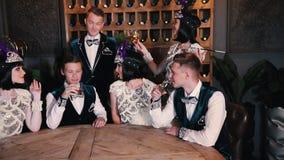 题材党-谈话闪耀的衣裳的年轻人坐在桌后和,当喝时 股票录像