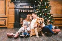 题材圣诞节和新年家庭圈子 与1岁儿童狗品种拉布拉多金毛猎犬的年轻白种人家庭 免版税图库摄影
