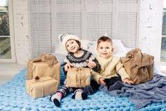 题材圣诞节早晨 两儿童白种人男孩和女孩兄弟和姐妹坐在容忍的床与微笑和 图库摄影