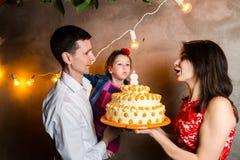 题材家庭假日儿童的生日和吹灭在大蛋糕的蜡烛 站立和举行5的年轻三口之家人 免版税库存图片