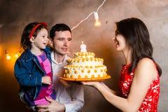 题材家庭假日儿童的生日和吹灭在大蛋糕的蜡烛 站立和举行5的年轻三口之家人 图库摄影