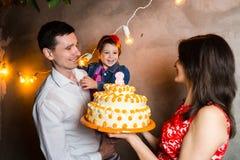 题材家庭假日儿童的生日和吹灭在大蛋糕的蜡烛 站立和举行5的年轻三口之家人 免版税库存照片