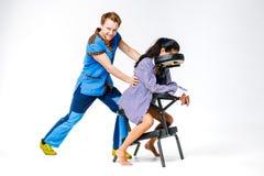 题材按摩和办公室 有微笑的治疗师的一个年轻人蓝色衣服的做着和少妇工作者的, b脖子按摩 免版税库存照片