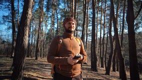 题材旅游业和技术 有胡子和背包的年轻白种人人 远足游人在杉木森林使用技术,手 免版税库存图片