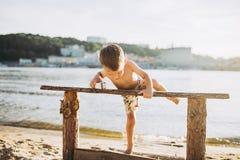 题材是一个儿童和夏天海滩假期 一个小白种人男孩在河岸的一个长木凳爬上一个晴朗的总和的 库存照片