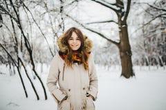 题材是一个周末假日在冬天 站立在夹克的雪公园的美丽的年轻白种人妇女有敞篷和毛皮的在牛仔裤a 免版税库存照片