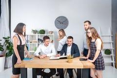 题材是事务和配合 召开会议,简报的一个小组年轻白种人人办公室工作者,与纸一起使用 库存图片