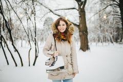 题材是周末假日在冬天 一名美丽的年轻白种人妇女在夹克的一个积雪的公园站立有敞篷和毛皮的 免版税库存图片