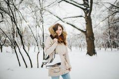 题材是周末假日在冬天 一名美丽的年轻白种人妇女在夹克的一个积雪的公园站立有敞篷和毛皮的 库存图片