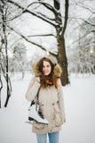 题材是周末假日在冬天 一名美丽的年轻白种人妇女在夹克的一个积雪的公园站立有敞篷和毛皮的 免版税图库摄影