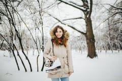 题材是周末假日在冬天 一名美丽的年轻白种人妇女在夹克的一个积雪的公园站立有敞篷和毛皮的 图库摄影