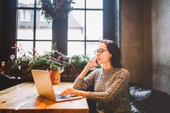 题材是小企业 工作在用圣诞节装饰装饰的咖啡店的一台便携式计算机后的一名年轻自由职业者的妇女 免版税库存照片