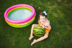 题目适当的健康吃的孩子 小女婴4岁在拥抱大绿色回合的绿草的白种人开会是 免版税库存图片