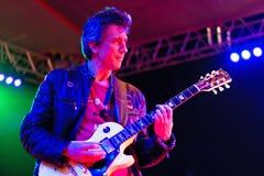 颜色下吉他弹奏者地点 免版税库存照片