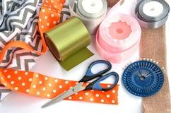 颜色丝带、剪刀和别针做的平的位置在白色背景 免版税库存照片