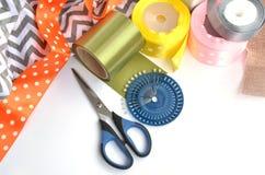 颜色丝带、剪刀和别针做的平的位置在白色背景 库存图片