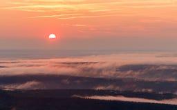 颜色使充满活力红色的日落环境美化 有薄雾的谷的看法 免版税库存照片
