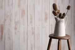 颜色卡片和花瓶在一把凳子在蓝色背景 免版税图库摄影