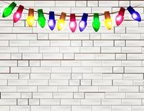 颜色在白色砖背景的圣诞灯电灯泡串  免版税库存照片