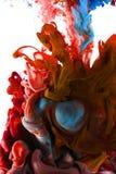 颜色墨水下落在水中 青玉蓝色,火红 免版税库存图片