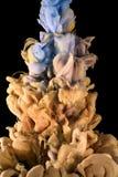 颜色墨水下落 液体 金子,蓝色上面 免版税库存图片