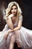 颜色婚礼礼服的美丽的白肤金发的年轻新娘妇女 岩石样式 库存照片