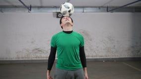 颜色对比地下作用停车 年轻灵巧的足球人训练橄榄球把戏 转动在手指的球 股票视频