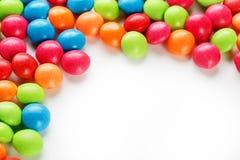 颜色彩虹从多彩多姿的糖果特写镜头,在白色背景的多彩多姿的釉糖衣杏仁的 库存图片