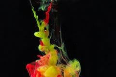 颜色油漆下落在水中 打旋的墨水在水面下 库存照片